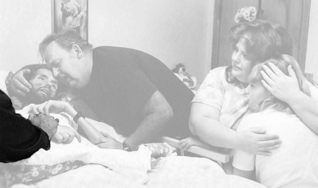 Fotografía de Therese Frare, David Kirby en el lecho de muerte, detalle mano de su cuidador, Peta