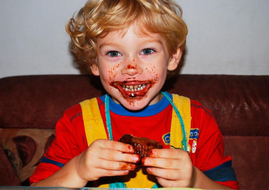 Niño sonriente comiendo chocolate, luz dura de flash