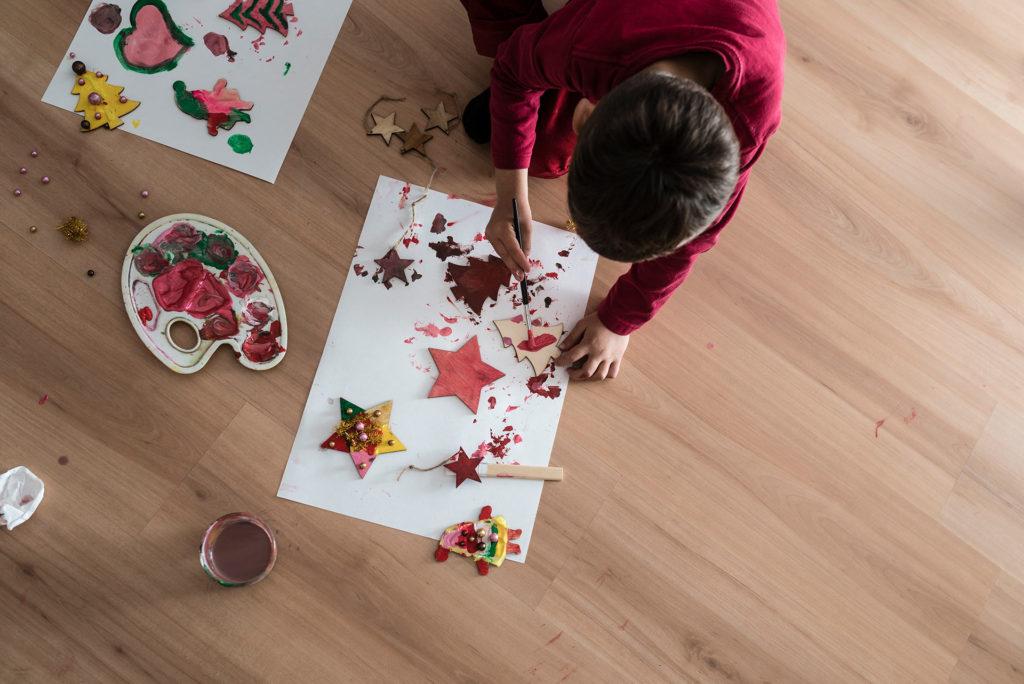 Niño pintando adornos navidad